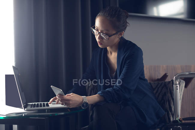 Woman using mobile phone and laptop at table in office — Stock Photo
