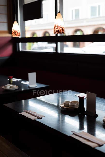 Table de sushi arrangée dans un restaurant par une journée ensoleillée — Photo de stock