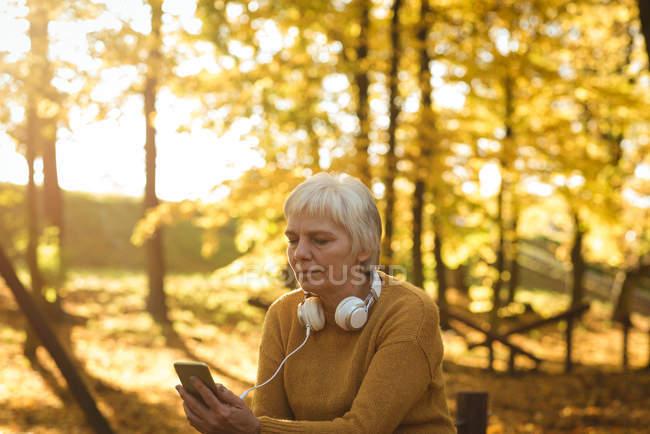Mujer mayor usando su teléfono móvil en el parque en un día soleado - foto de stock
