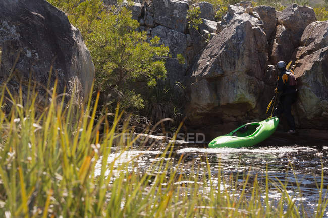 Mulher, puxando o caiaque barco na costa rochosa. — Fotografia de Stock