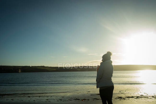 Young woman standing near river side during sunset. — Stock Photo