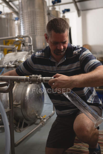 Male worker filling gin in measuring cylinder from distillery in factory — Stock Photo