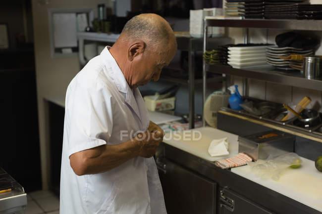 Старший повар, носить его форму в кухне в ресторане — стоковое фото