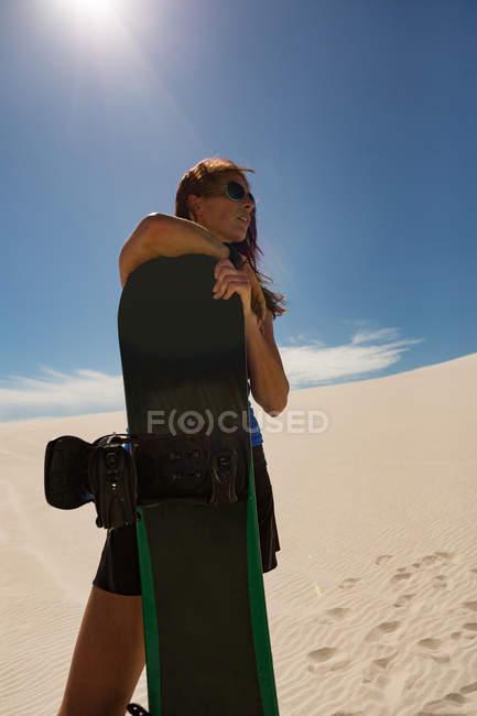 Femme avec sandboard debout dans le désert par une journée ensoleillée — Photo de stock