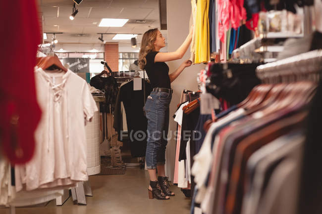 Beautiful girl shopping for clothes in mall — Stock Photo