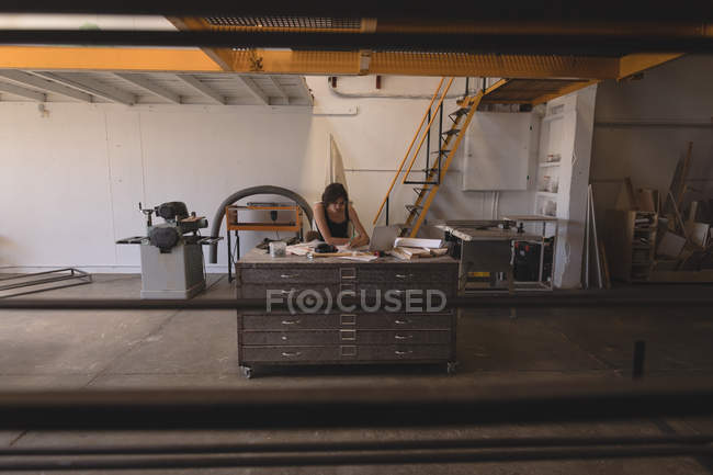 Female artisan working with blueprints at desk in workshop interior. — Stock Photo
