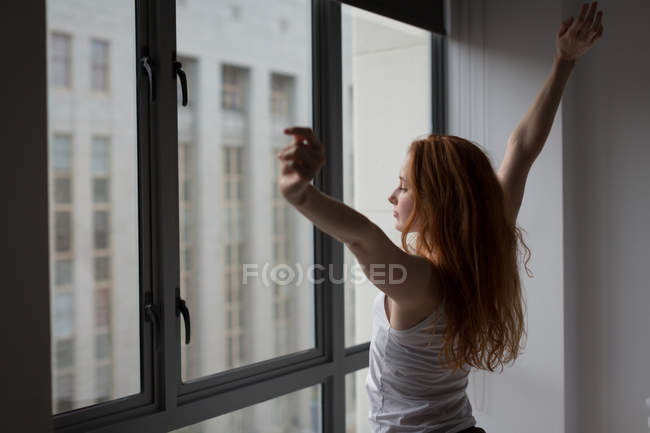 Young woman standing with arms outstretched at home — Stock Photo