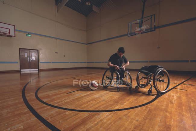 Инвалид регулирует пояс инвалидной коляски в суде — стоковое фото