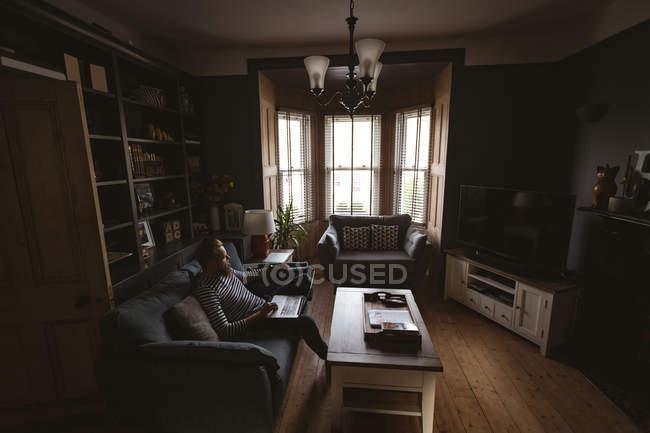 Мужчина, сидящий дома на диване с ноутбуком — стоковое фото