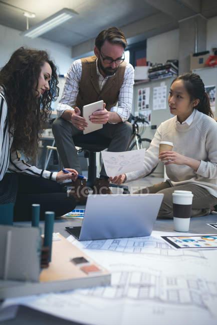 Executivos discutindo sobre o documento no escritório moderno — Fotografia de Stock