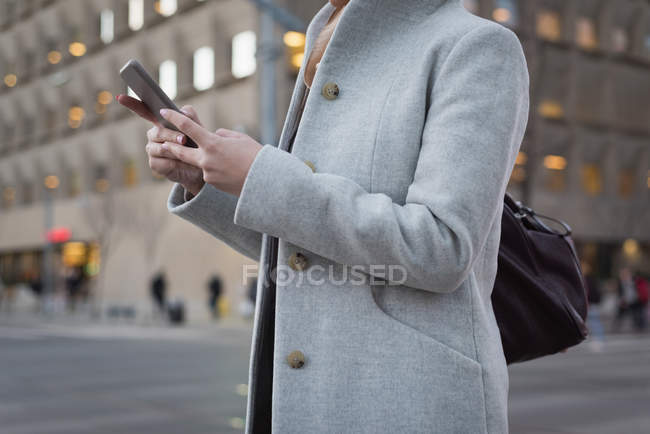 Mid section of woman using mobile phone at railway station — Stock Photo