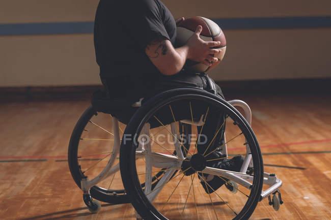 Faible section de l'homme handicapé tenant basket-ball dans le tribunal — Photo de stock