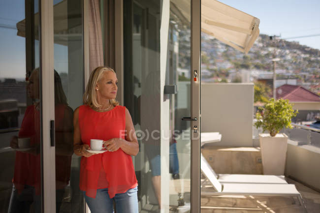 Disabled woman holding cup of coffee in balcony at home. — Stock Photo