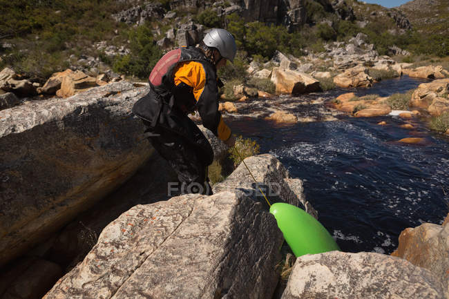 Woman pulling kayak boat on rocks by river. — Stock Photo