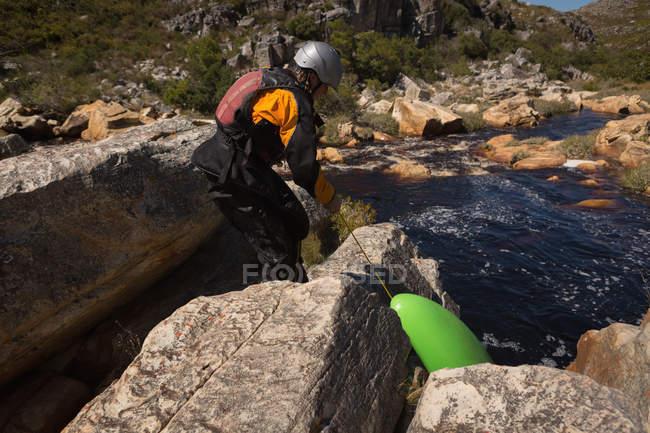 Женщина, потянув каяк лодки на скалах у реки. — стоковое фото