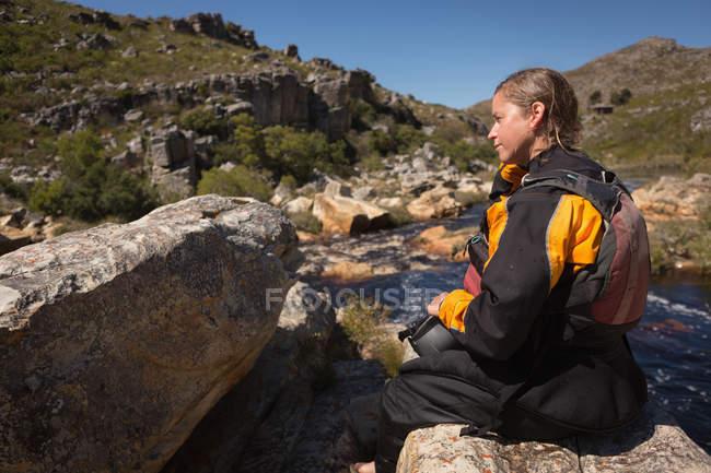 Kayaker feminino pensativo sentado em rochas por rio . — Fotografia de Stock