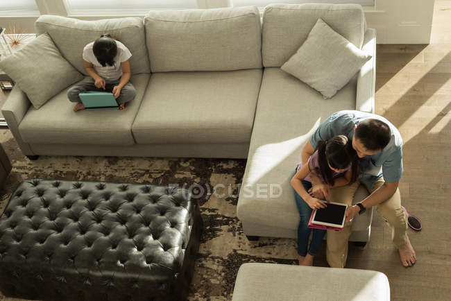 Girl using digital tablet with her father in living room at home — Stock Photo