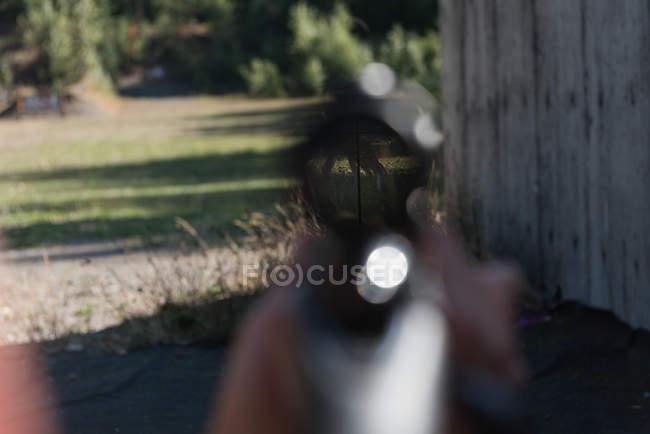 Embaçado homem apontando o rifle sniper no alvo no tiro ao alvo em um dia ensolarado — Fotografia de Stock