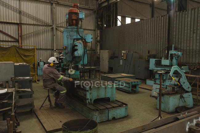Работник, использующий фрезерный станок в мастерской — стоковое фото