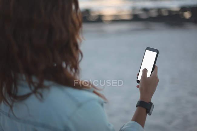 Вид сзади женщины с мобильного телефона на пляже — стоковое фото