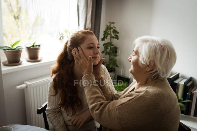 Бабушка трогает внучку дома. — стоковое фото