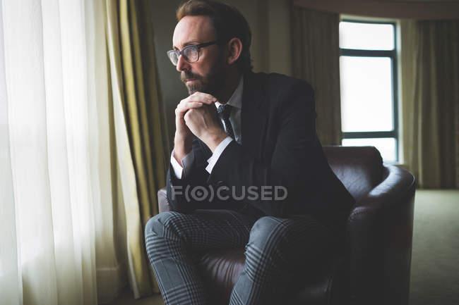 Продуманий бізнесмен, сидячи на крісло в готельному номері — стокове фото