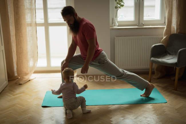 Bambino imitando suo padre mentre si esercita a casa — Foto stock