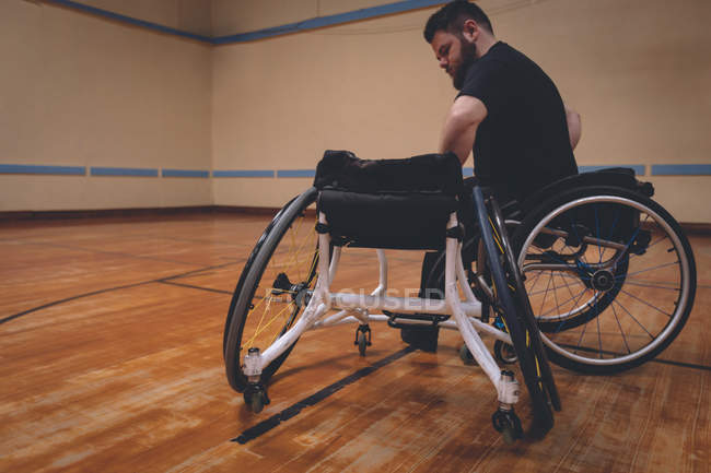 Disabled man operating wheelchair in the court — Stock Photo