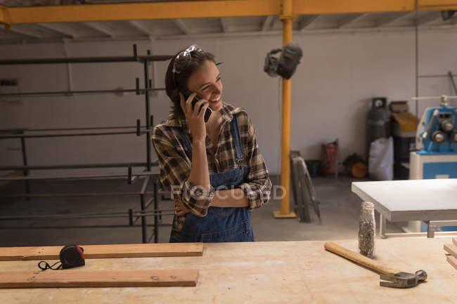 Junge Kunsthandwerkerin telefoniert in Werkstatt. — Stockfoto