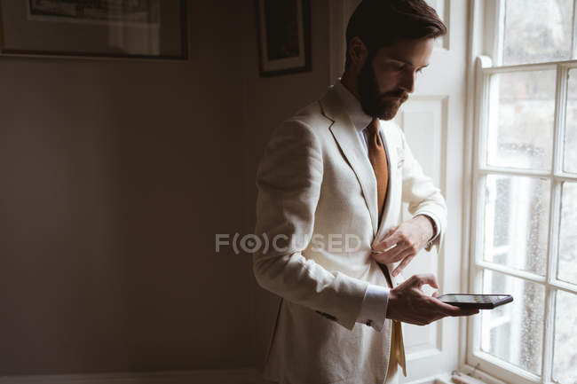 Groom usando telefone celular perto da janela em casa — Fotografia de Stock