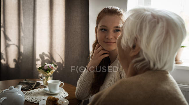 Grandmother and granddaughter interacting at home — Stock Photo