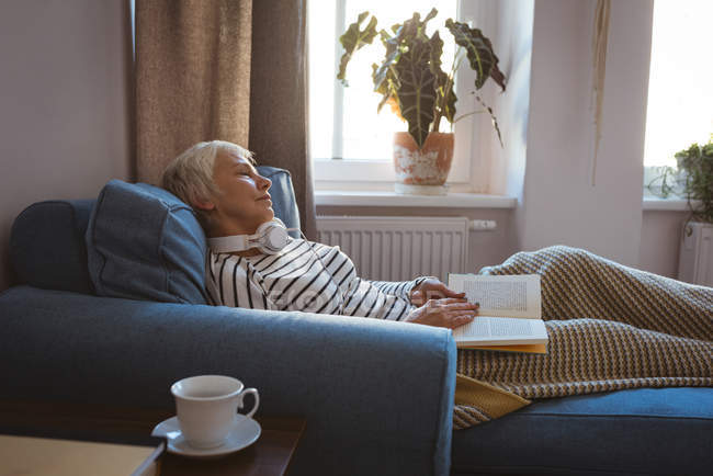 Senior woman taking a nap on the sofa while reading the book in living room at home — Stock Photo