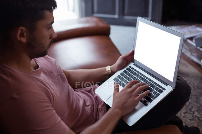 Male customer using laptop in barbershop — Stock Photo