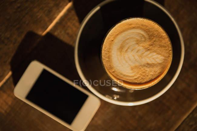 Sobrecarga de espresso cremoso sobre mesa de madera - foto de stock
