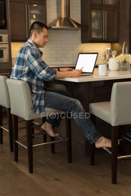 Мужчина использует ноутбук на кухне дома — стоковое фото