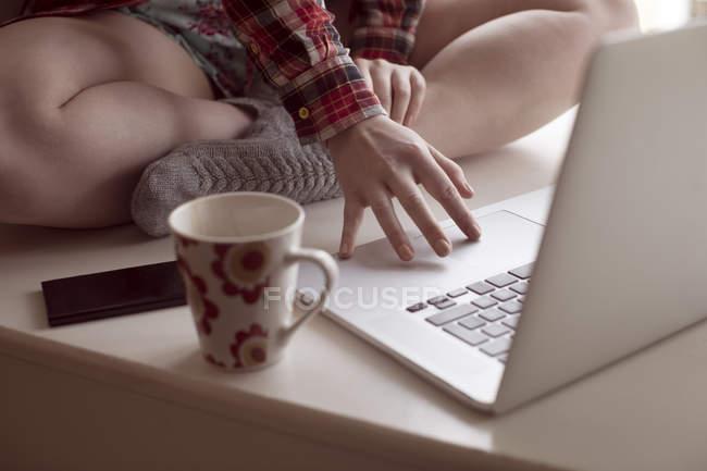 Primo piano della donna che utilizza il computer portatile a casa. — Foto stock
