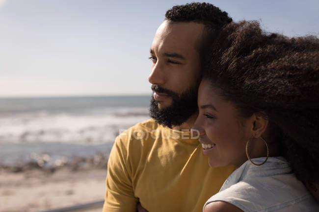 Lächelndes Paar am Strand an einem sonnigen Tag — Stockfoto