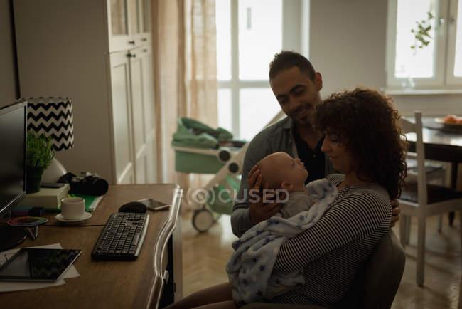 Родители, держа их ребенка в гостиной дома — стоковое фото