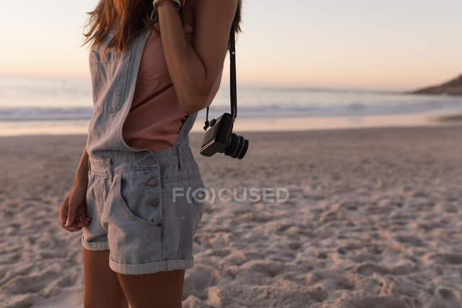 Partie médiane de la femme avec caméra vintage à la plage de sable au crépuscule — Photo de stock