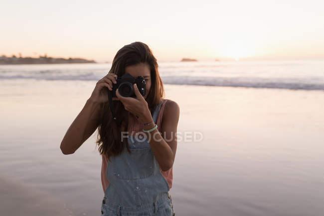 Femme prenant des photos avec appareil photo à la plage au crépuscule . — Photo de stock