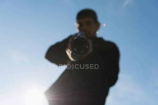 Hombre disparando con arma en un día soleado - foto de stock