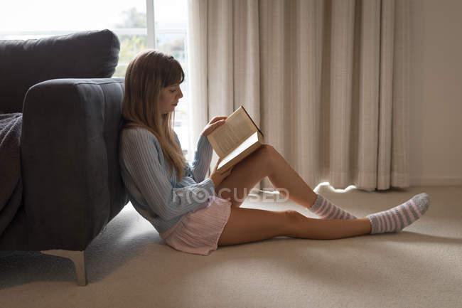 Женщина читает книгу в гостиной дома . — стоковое фото