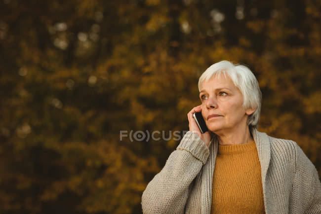 Senior woman using a smartphone in a park at dawn — Stock Photo