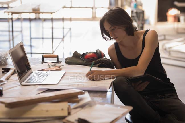 Donna artigianale lavora con le cianografie allo scrittorio in officina. — Foto stock