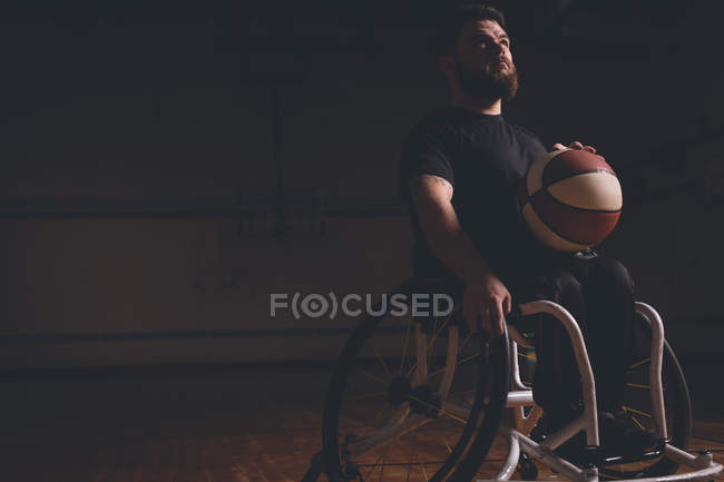 Thoughtful disabled man practicing basketball in the court — Stock Photo