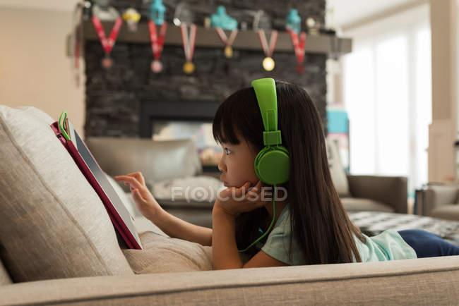 Femme avec écouteurs utilisant une tablette numérique à la maison — Photo de stock