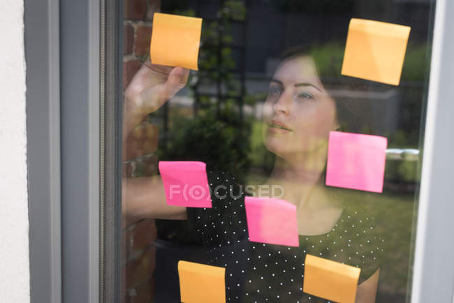 Female executive looking sticky notes in office — Stock Photo