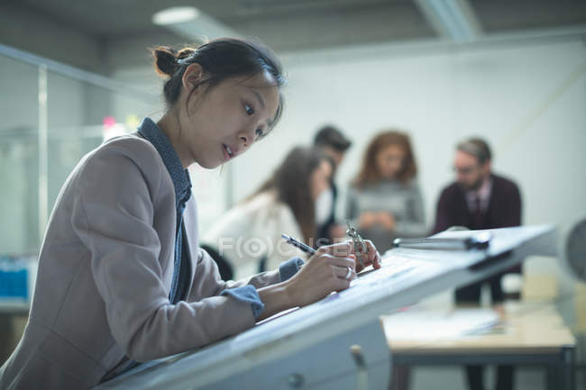 Female executive working over drafting table in office — Stock Photo