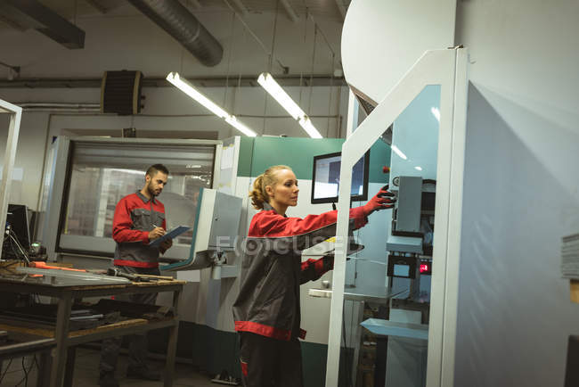 Two workers checking machine in factory — Stock Photo