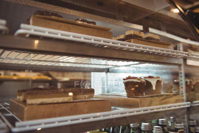 Variedade de pastelaria em prateleiras de exposição no café — Fotografia de Stock
